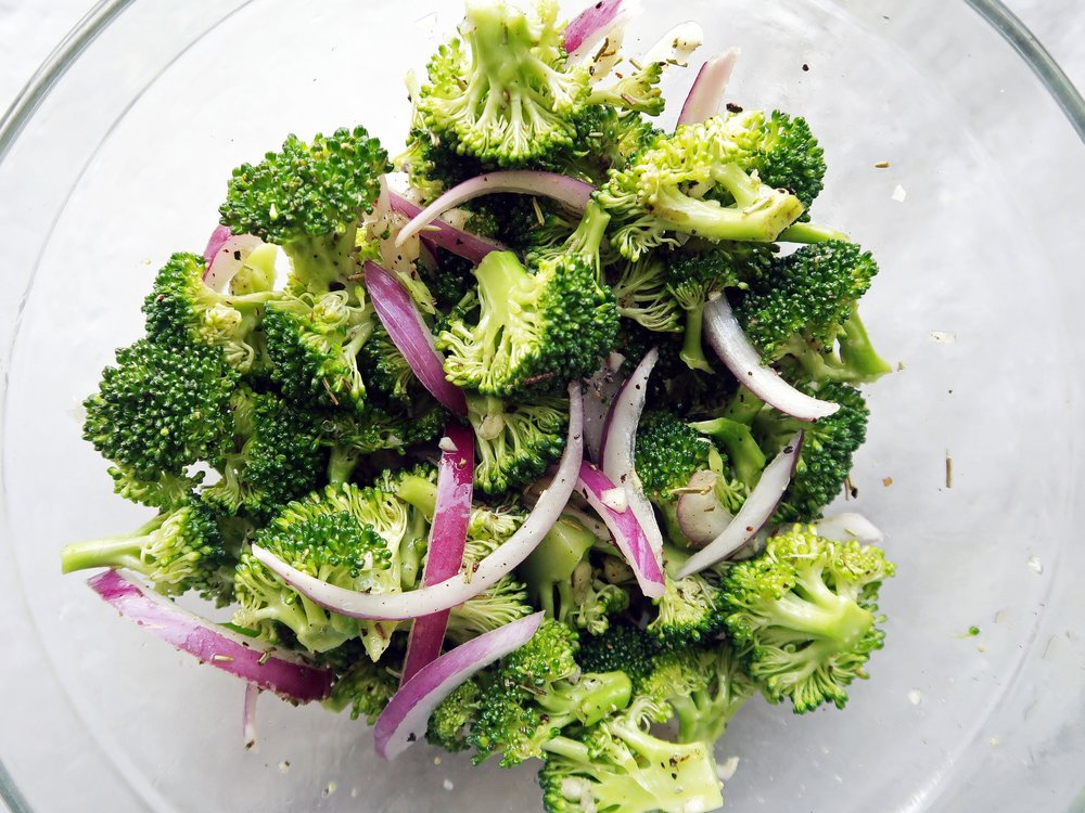 Broccoli, red onion slices, garlic, and herbs in a glass bowl.