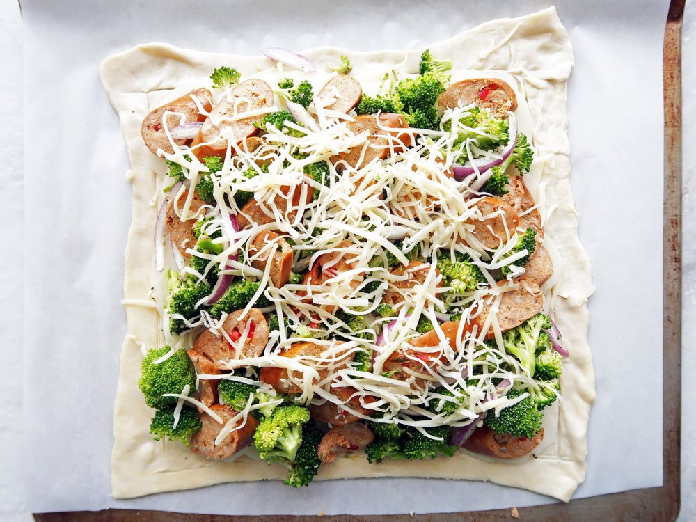 A sheet of puff pastry covered with potatoes, broccoli, sausage, and cheese.