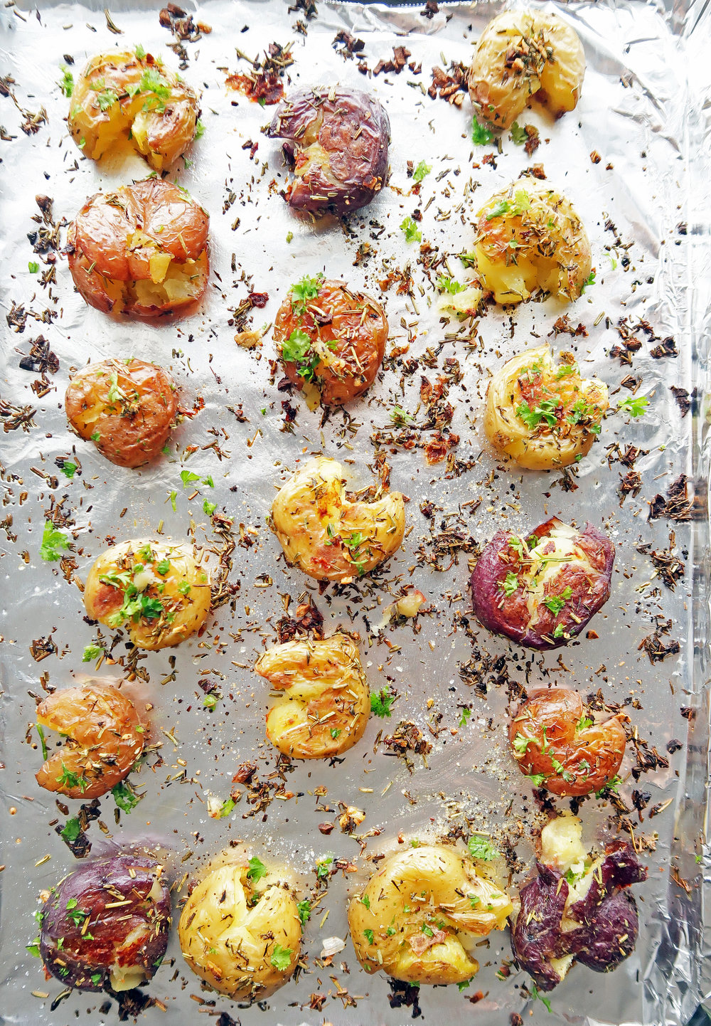 Vegan and gluten-free Crispy Garlic Smashed Baby Potatoes on a baking sheet.