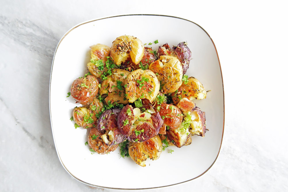 Crispy Garlic Smashed Baby Potatoes on a white plate; An easy, gluten-free, vegan side dish with a crispy outside and fluffy inside.