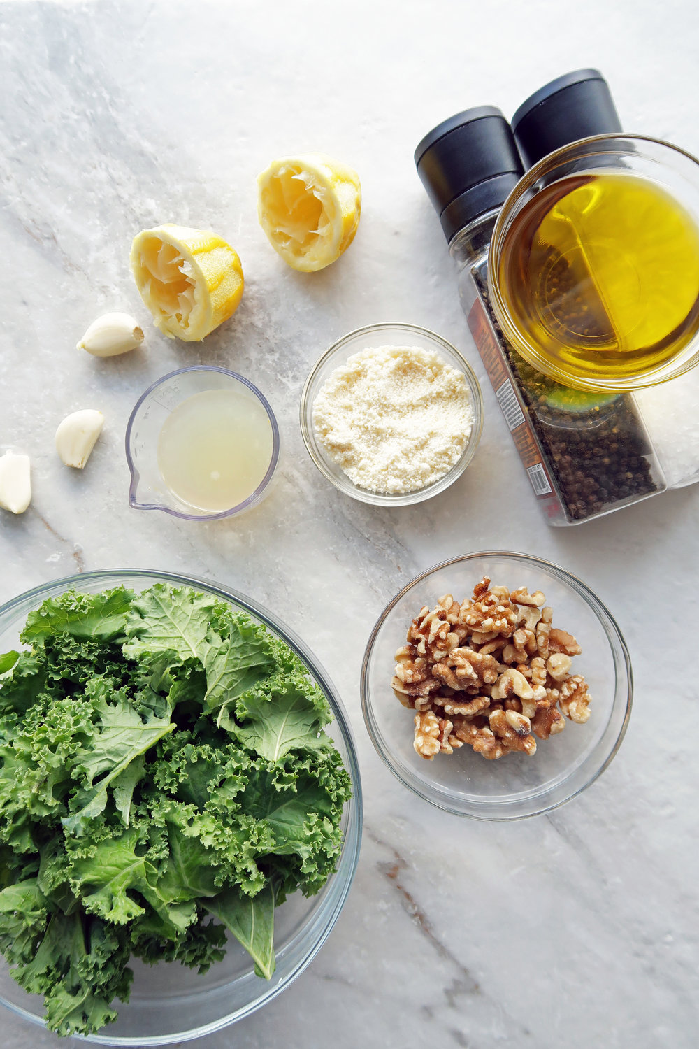 Bowls of kale, walnuts, olive oil, lemon juice, and parmesan cheese.