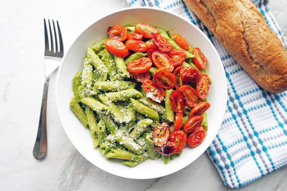 Pesto pasta with roasted tomatoes in a white bowl; a fork, kitchen towel, and french bread to its side.