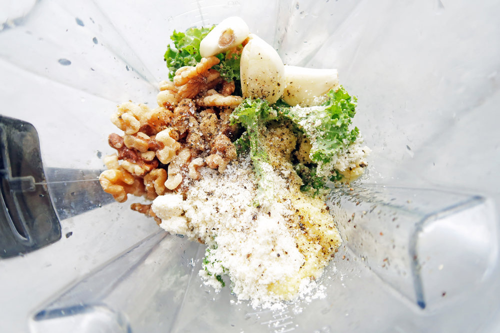 A blender containing kale walnut pesto ingredients.