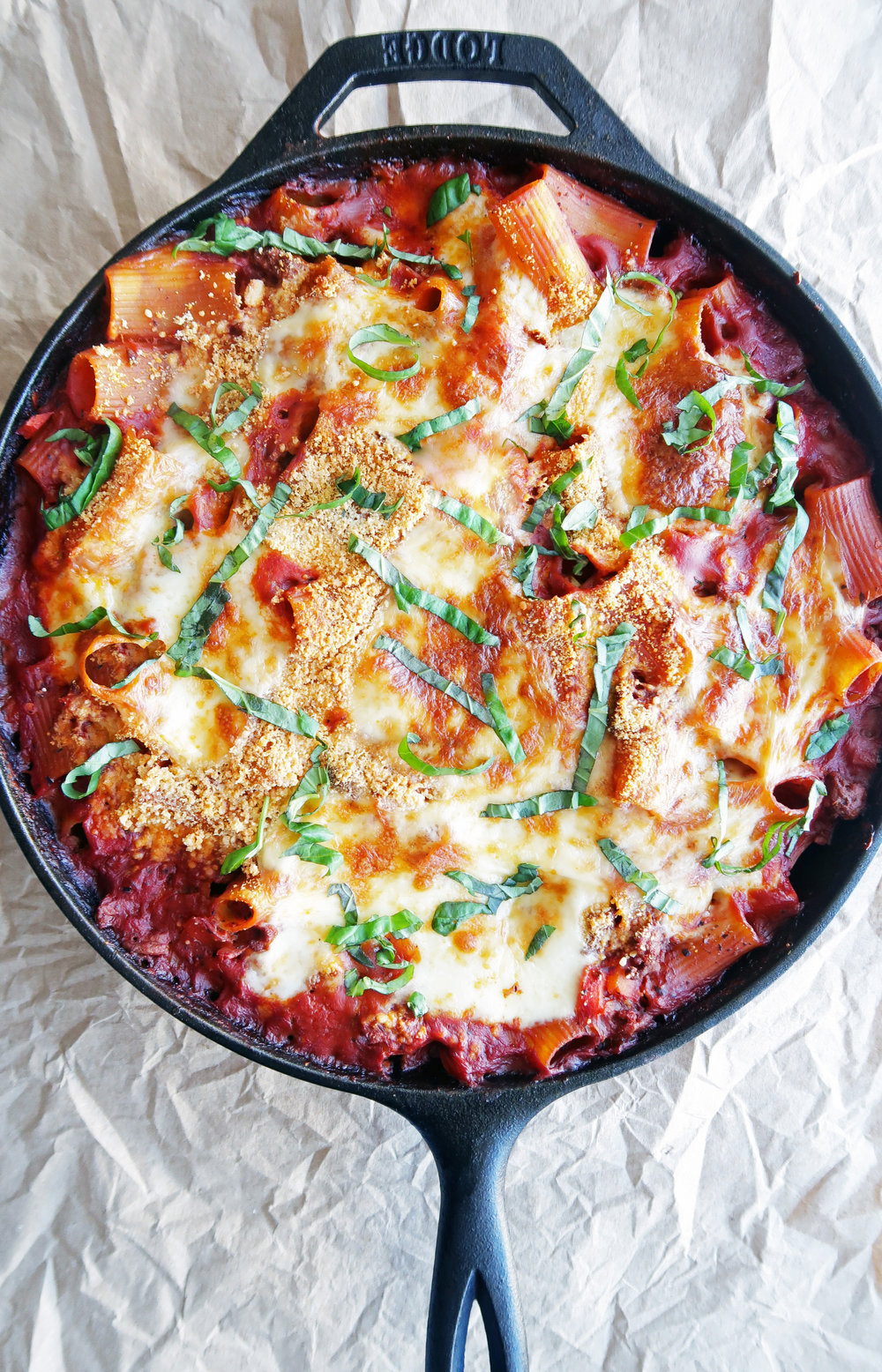 Baked Beef Pasta Casserole with melted cheesy topping and fresh basil in a cast-iron skillet.