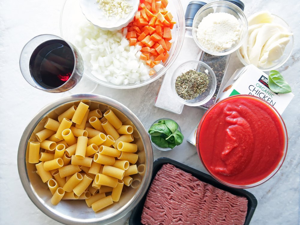 Bowls of dry rigatoni, chopped onions and peppers, cheese, crushed tomatoes, and herbs next to ground beef.