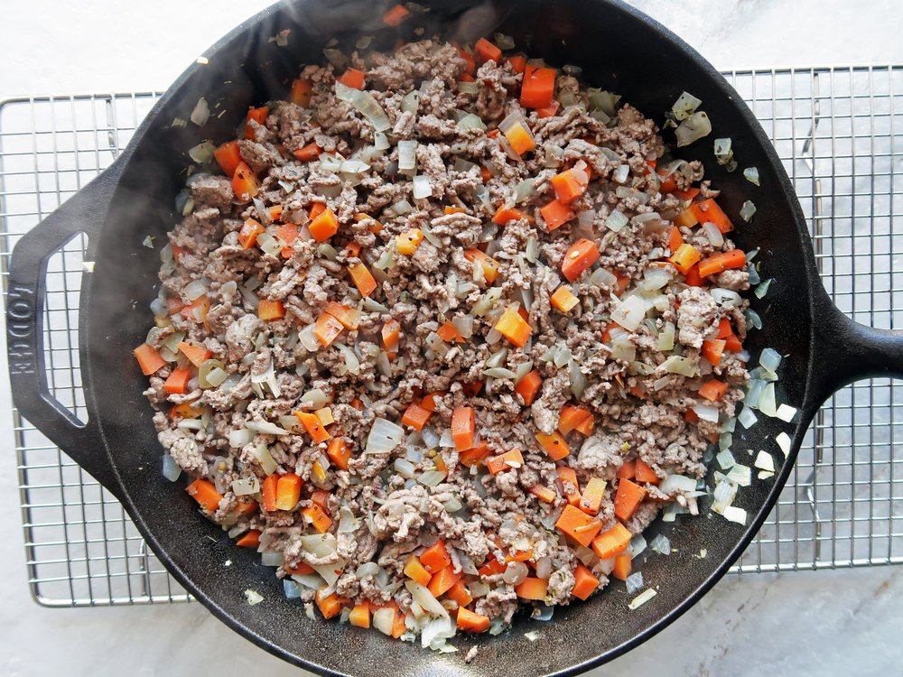 A cast iron skillet full of sauteed ground beef, chopped onions, and bell peppers.