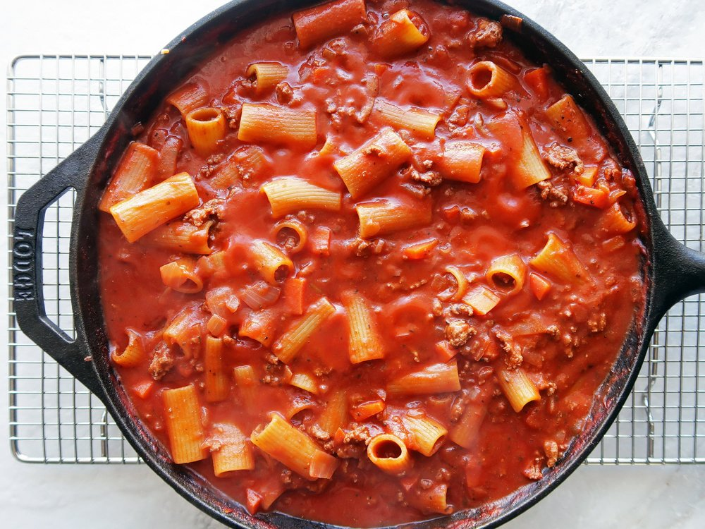 A cast iron skillet full of rigatoni with covered in meat sauce.