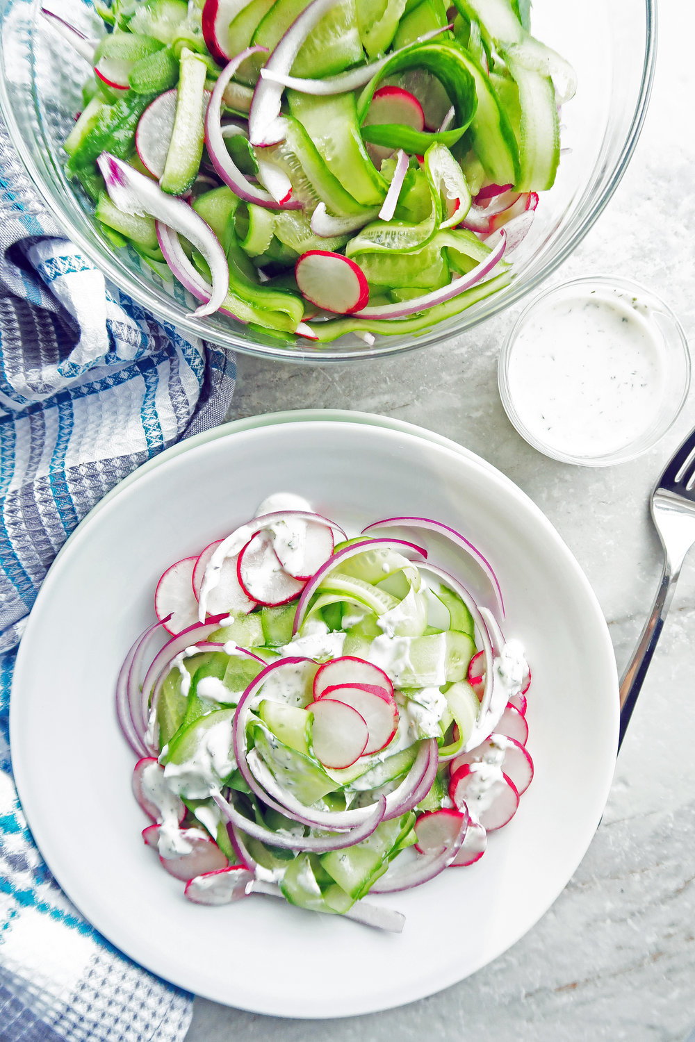 Shaved Cucumber Salad with Lime-Mint Yogurt Dressing on a white plate with more undressed salad, dressing, and fork to its side.