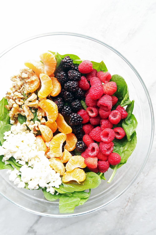 A bowl of spinach, blackberries, raspberries, mandarin oranges, walnuts, and feta.