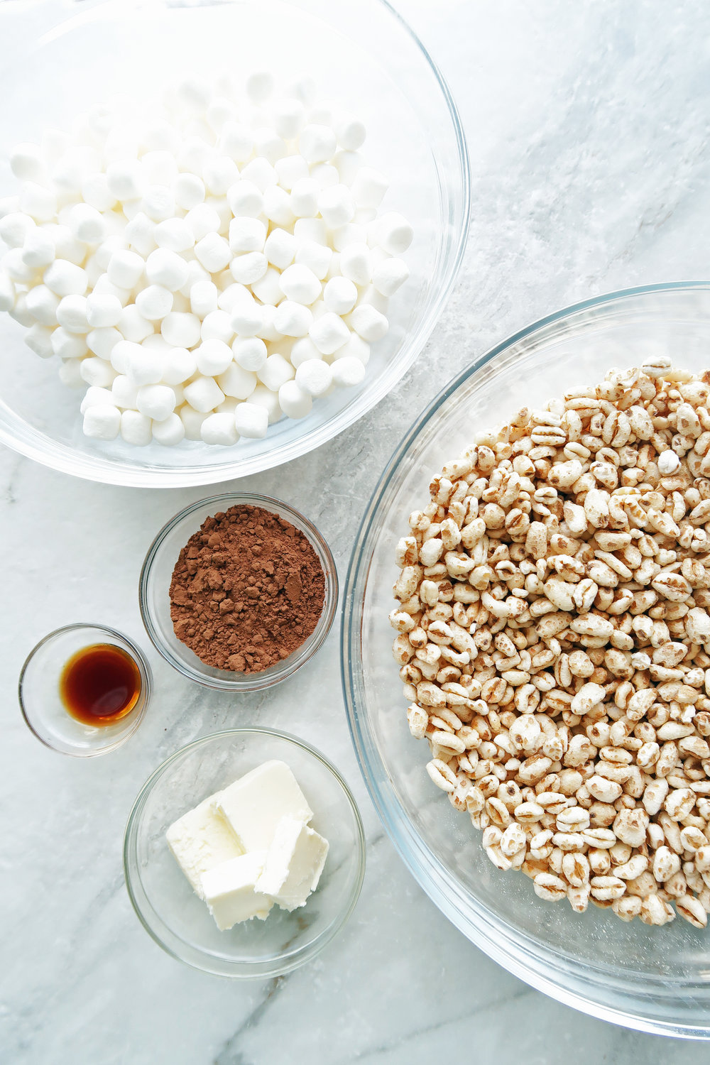 Bowls of puffed wheat, marshmallows, cocoa powder, butter, and vanilla extract.