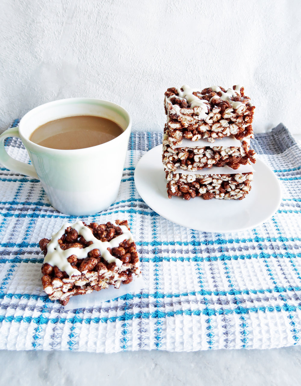 Three Chocolate Marshmallow Puffed Wheat Squares stacked on a white plate along with another puffed wheat square and cup of coffee beside the plate.