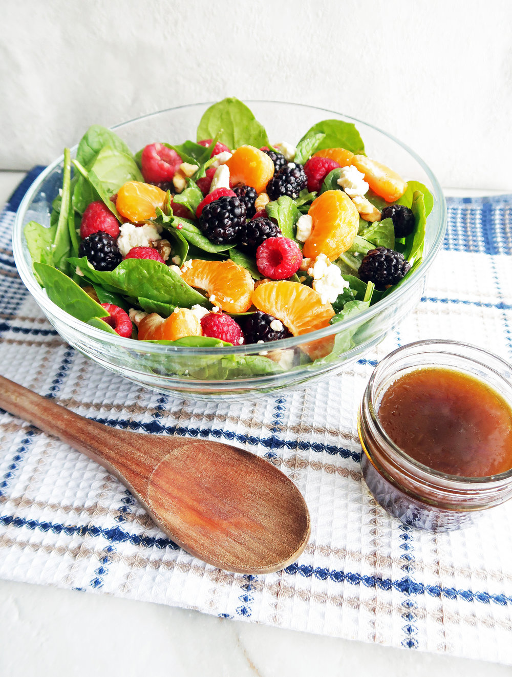 A glass bowl of Berry Orange Spinach Salad tossed in Citrus Balsamic Vinaigrette with more dressing in a small jar and a wooden spoon to the side.