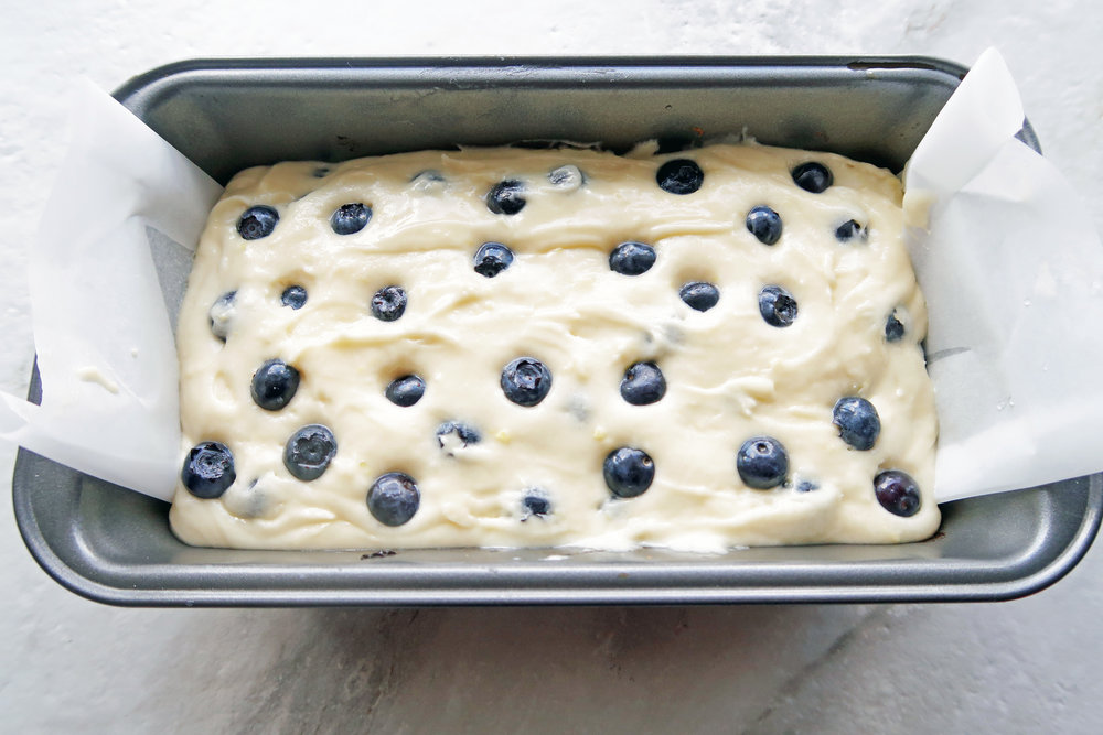 Lemon blueberry loaf cake batter in a loaf pan with more blueberries on top, ready for the oven.
