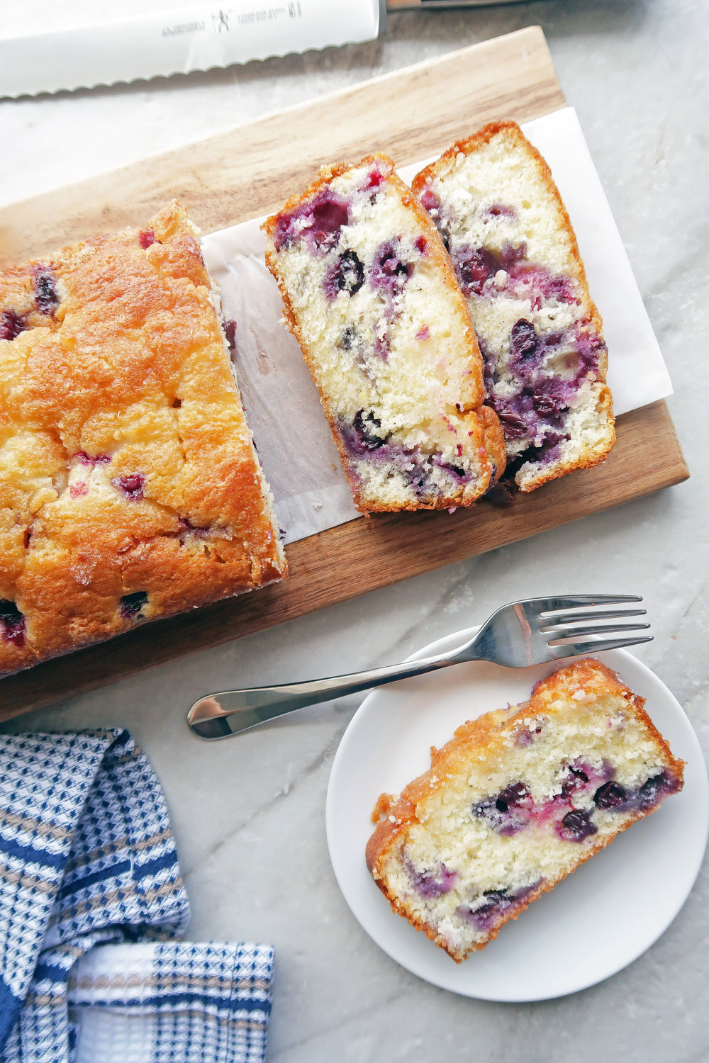 Piece of Classic Lemon Blueberry Loaf Cake on a white plate with fork; the remaining loaf cake on a long wooden board.