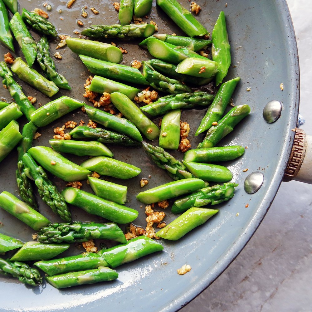 A saute pan featuring asparagus and garlic.