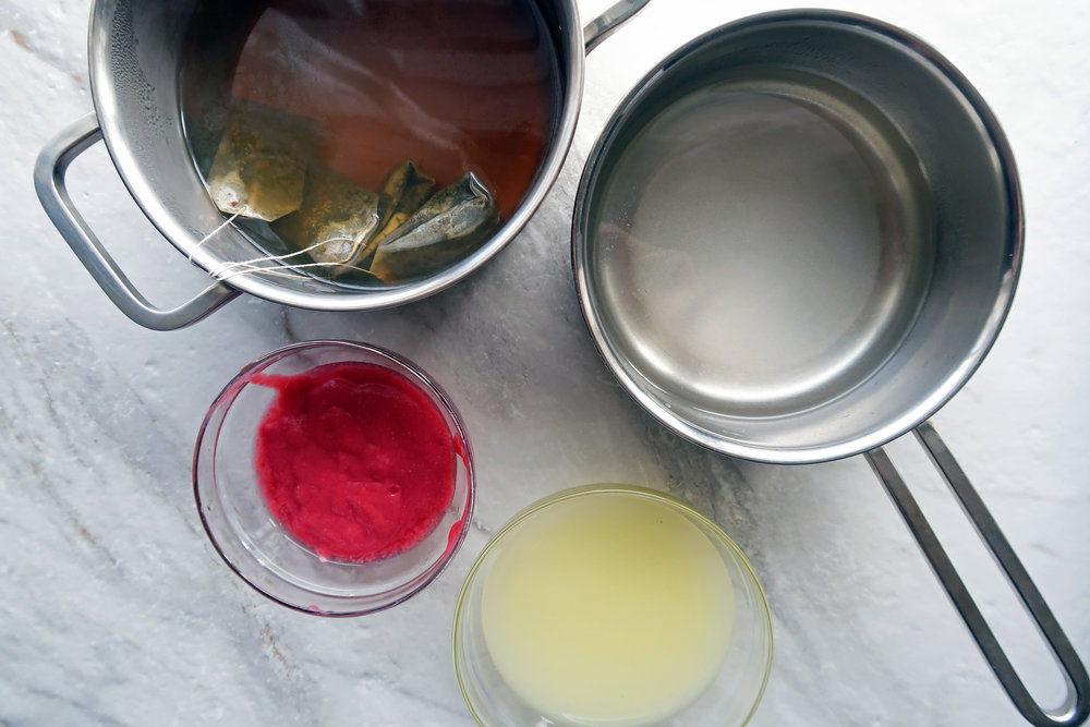 Pots of stepped green tea and simple syrup with bowls of lemon juice and raspberry puree.
