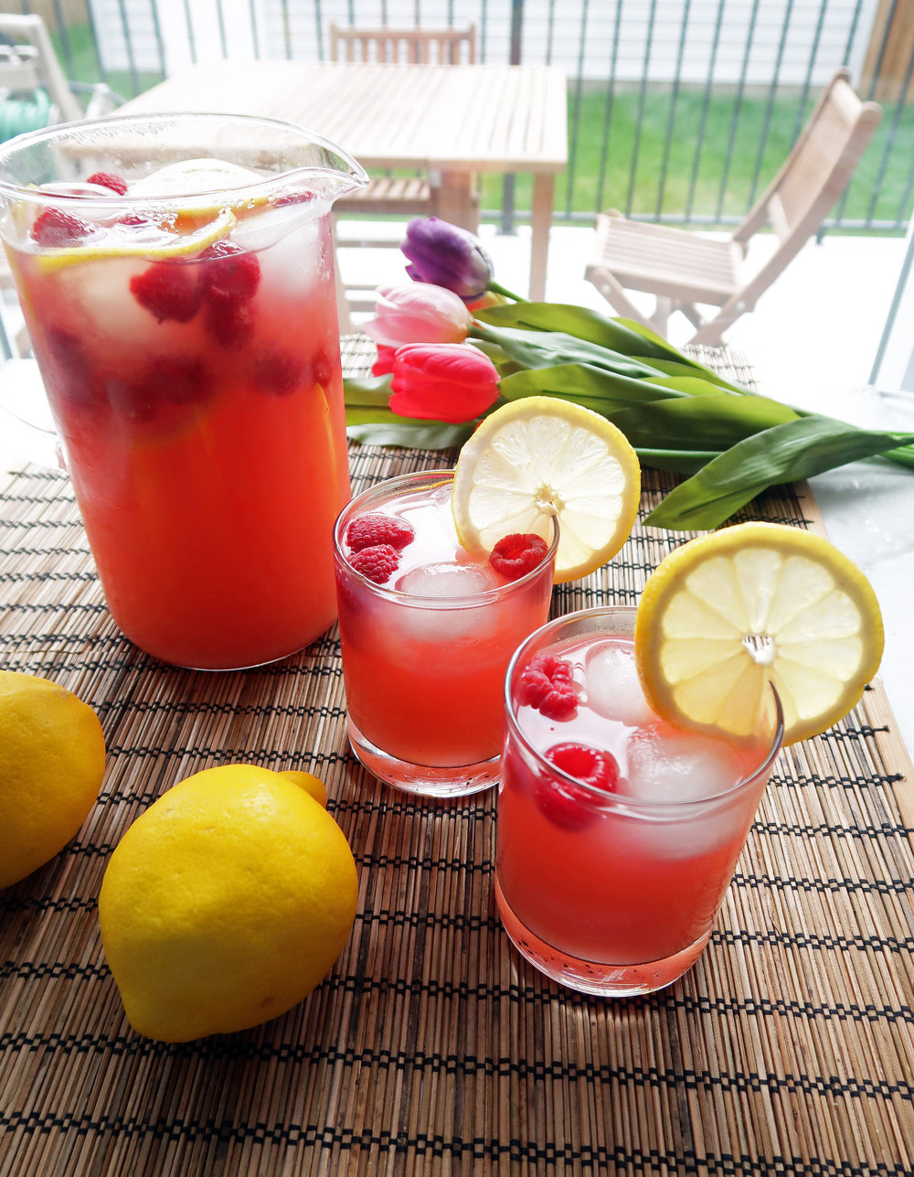 Two glasses and a pitcher full of homemade Raspberry Green Tea Lemonade with lemon slices and raspberry garnish; lawn chairs and table in the background.
