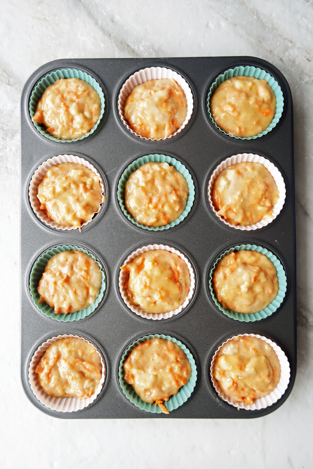 Pineapple carrot muffin batter placed in a dozen silicone liners in a muffin tin.