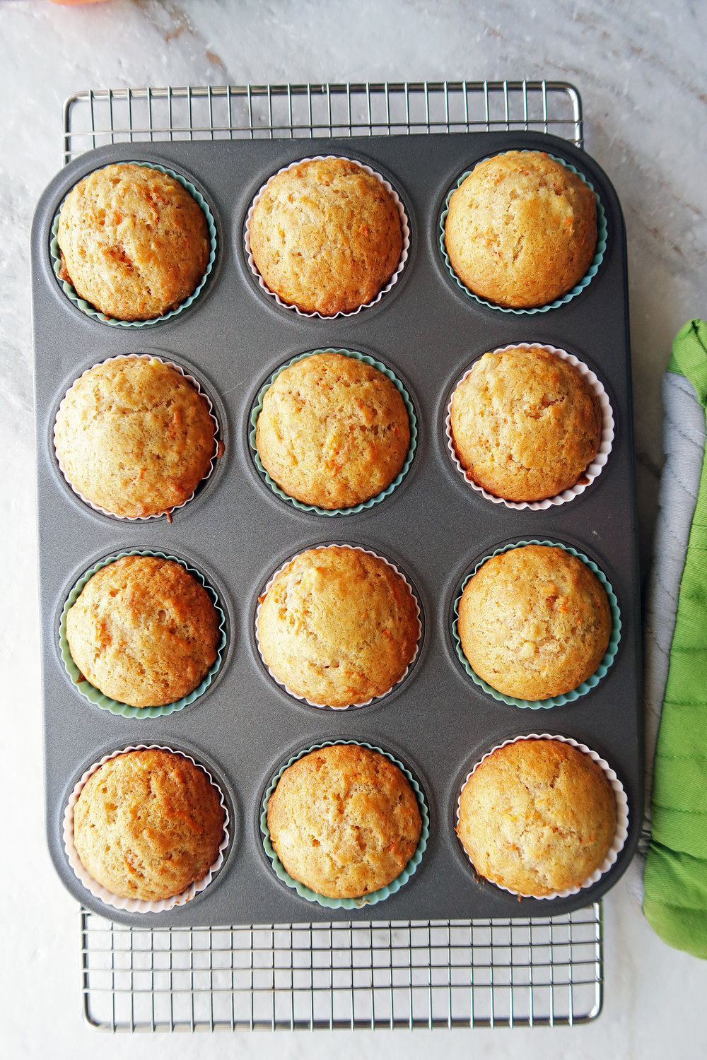 A dozen golden brown baked Easy Carrot Pineapple Muffins in a muffin tin.