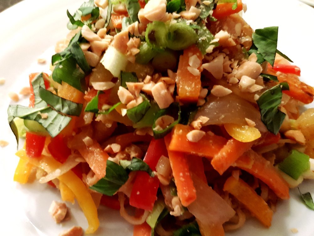 Overhead close-up of Vegetable Pad Thai topped with Thai basil and peanuts.
