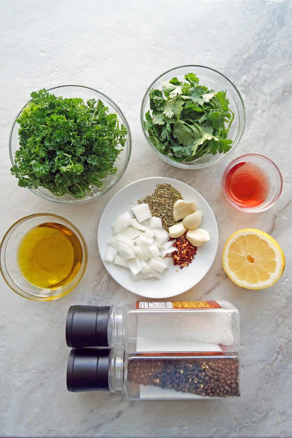 Bowls of parsley, cilantro, olive oil, and red wine vinegar alongside a lemon, chopped onions, garlic, oregano, and red pepper flakes.