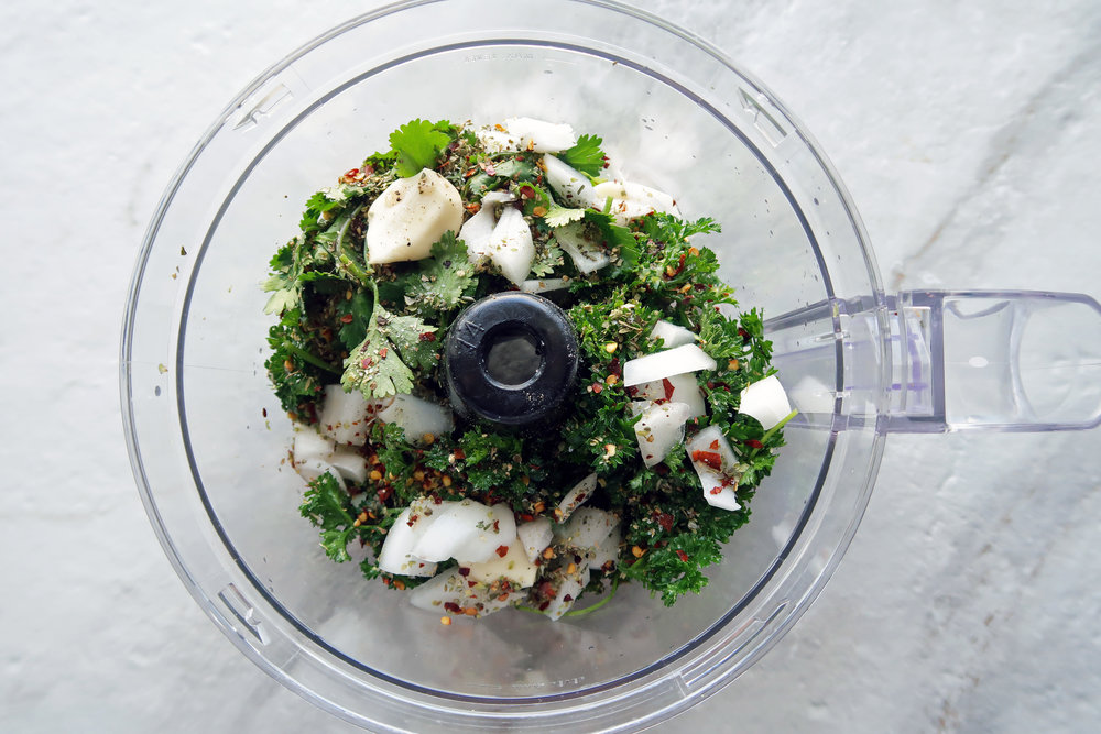 A food processor containing chimichurri sauce ingredients.