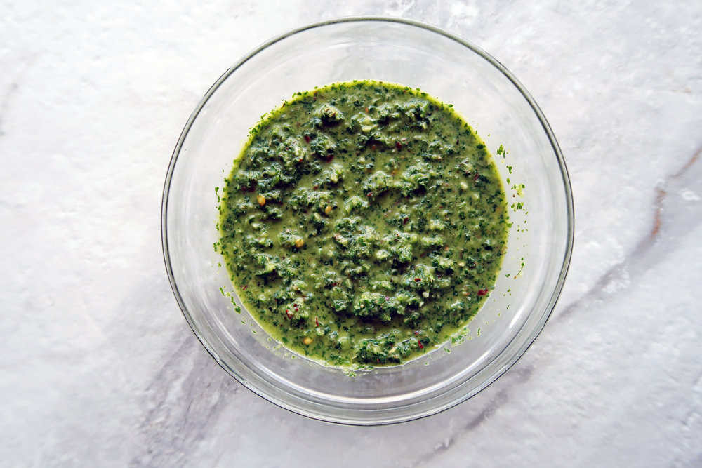 Freshly blended chimichurri sauce in a food processor.