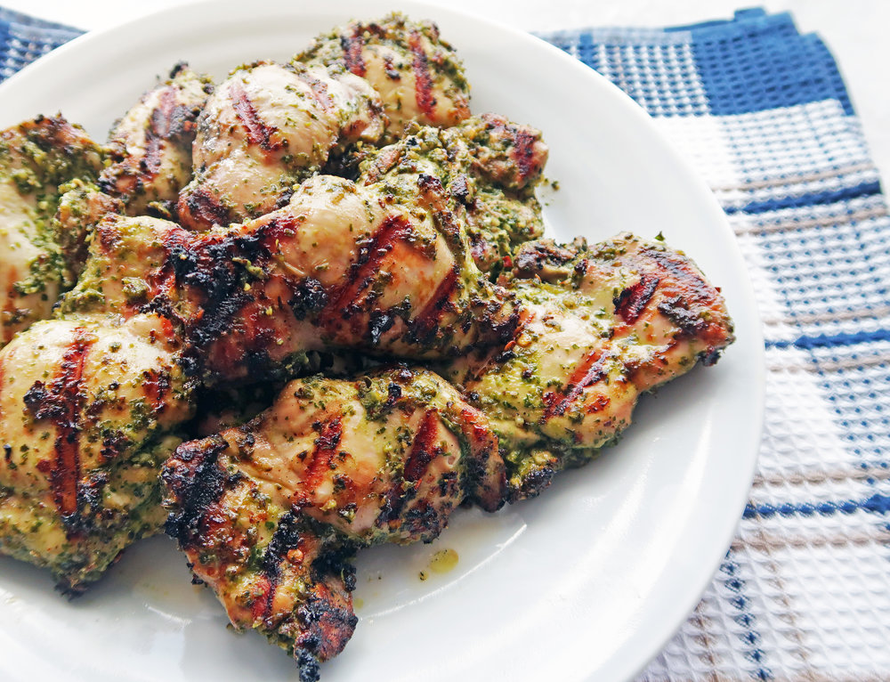 Side angled view of a white plate Grilled Chicken Thighs with Chimichurri Sauce on top of a blue checkered towel.