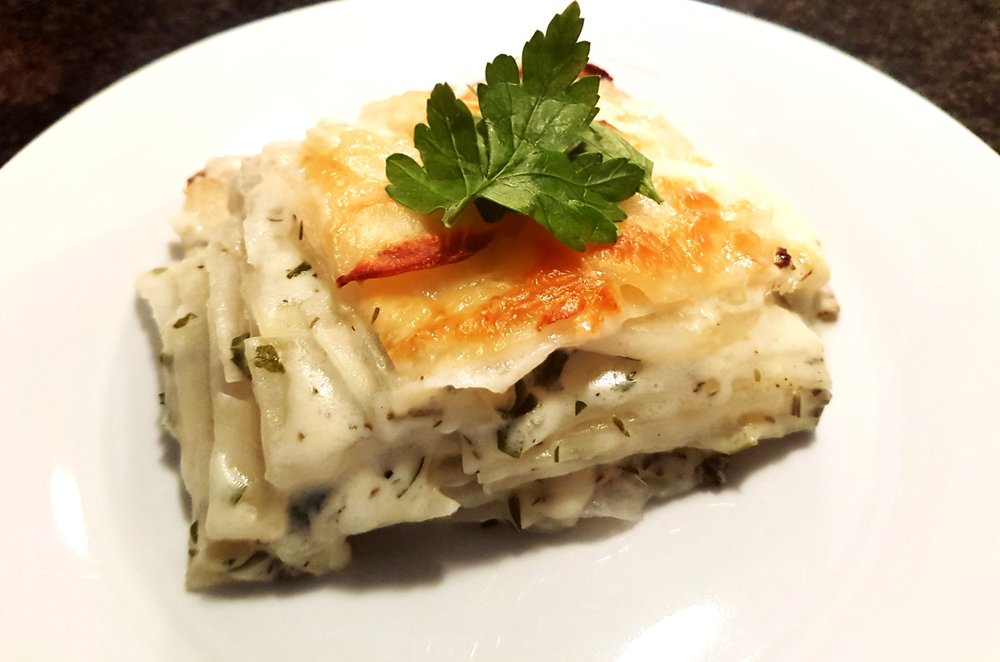 a hot piece of Creamy Potato Cheese Gratin on a plate revealing layers of potatoes and a crispy, golden brown top
