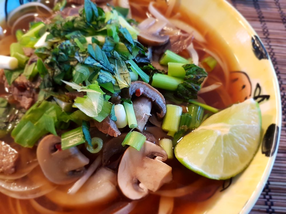 Vietnamese Noodles with Beef and Mushrooms topped with green onions and cilantro.