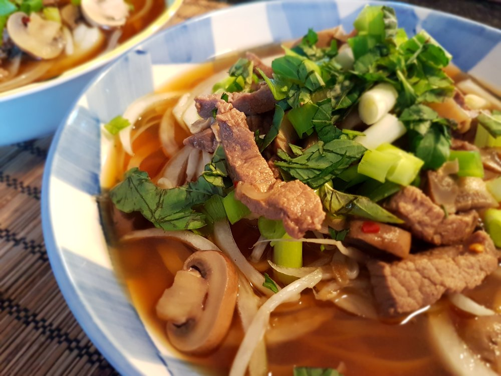 a hot bowl of Vietnamese Noodles with Beef and Mushrooms