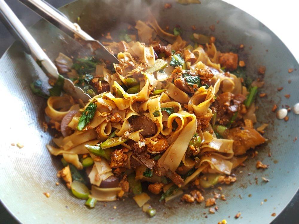 a sizzling wok full of Vegetarian Pad See Ew