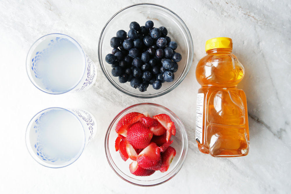 Bowls of strawberries, blueberries, and coconut water next to a bottle of honey.