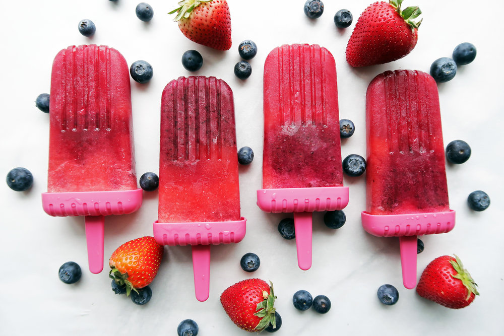 Four Strawberry Blueberry Coconut Water Popsicles placed side by side with strawberries and blueberries around them.
