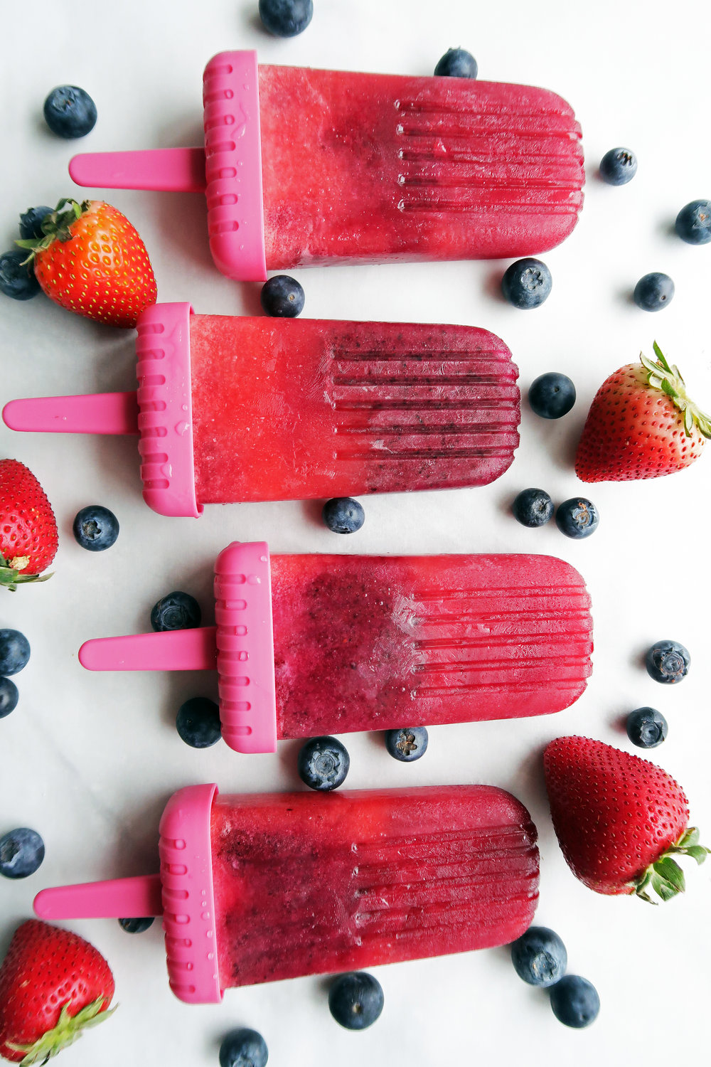 Four Strawberry Blueberry Coconut Water Popsicles laid side by side with blueberries and strawberries around them.