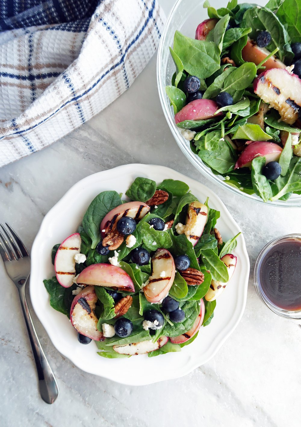 A overhead view of a fresh bowl of grilled peach blueberry spinach salad with honey balsamic vinaigrette on the side.