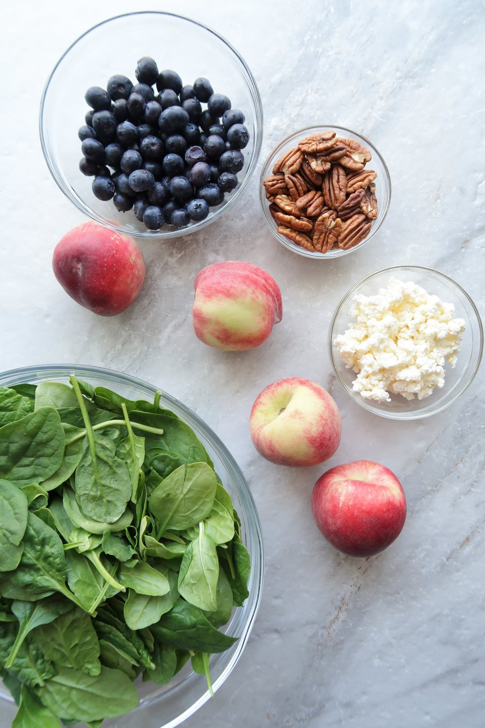 Glass bowls containing fresh blueberries, pecans, feta cheese, and spinach with four white peaches surrounding the bowls.