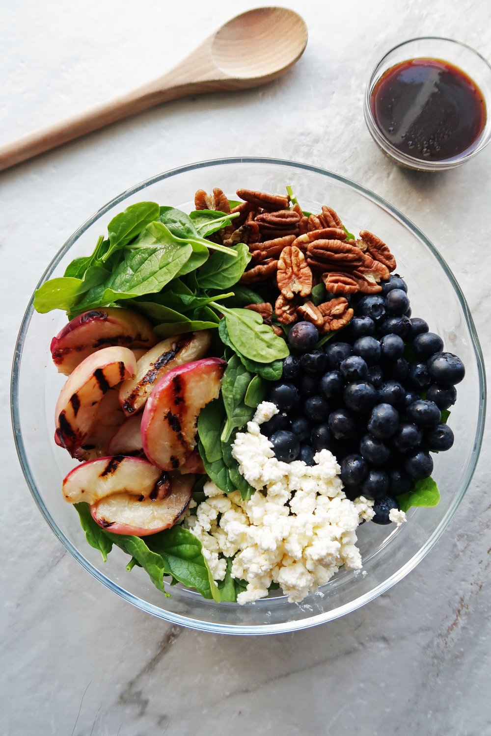 A big glass bowl of spinach covered with grilled peach slices, pecans, blueberries, and crumbled feta cheese with honey balsamic vinaigrette on the side.