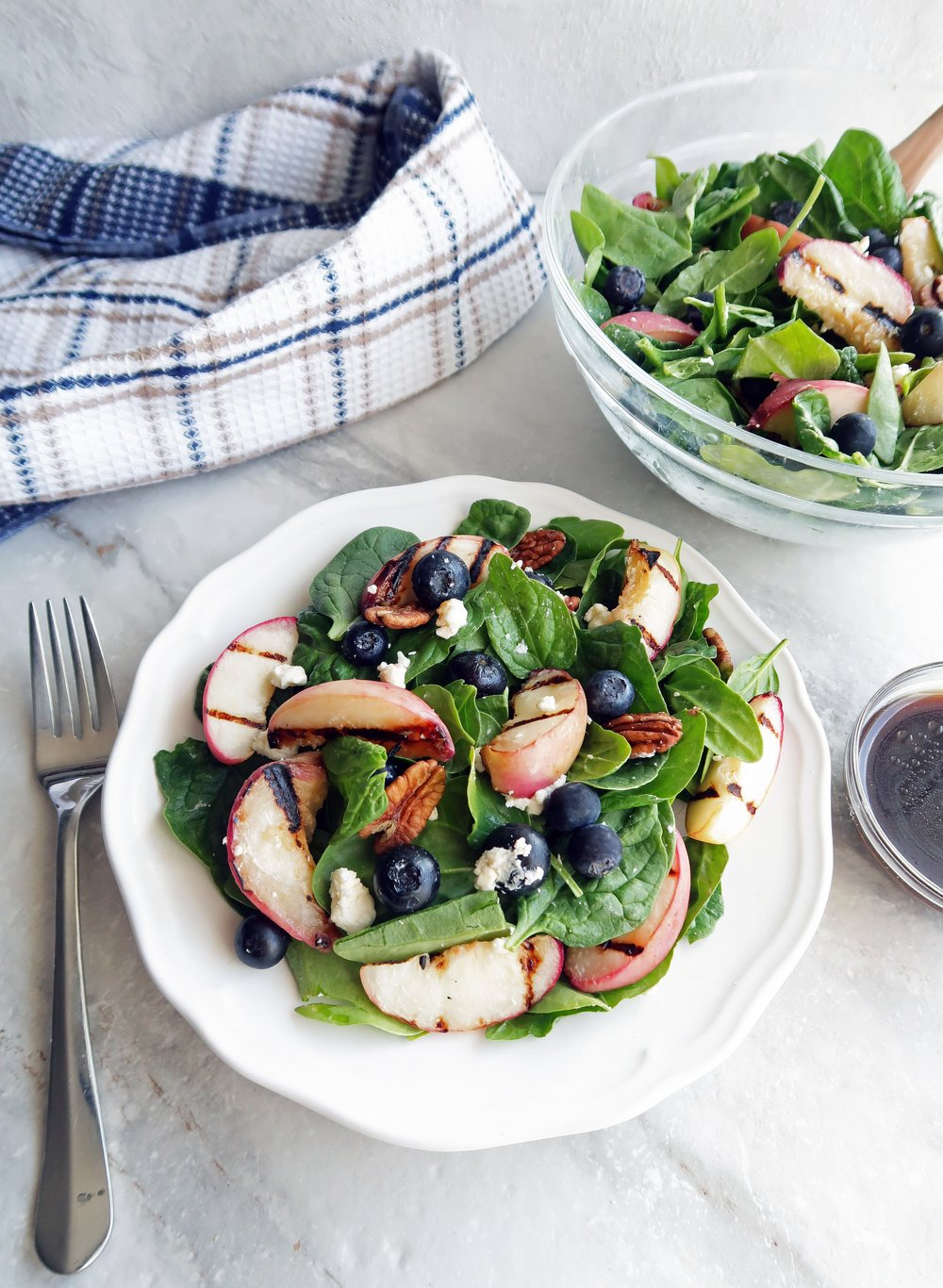 A plate of Grilled Peach Blueberry Spinach Salad with more salad and honey balsamic vinaigrette to the side.