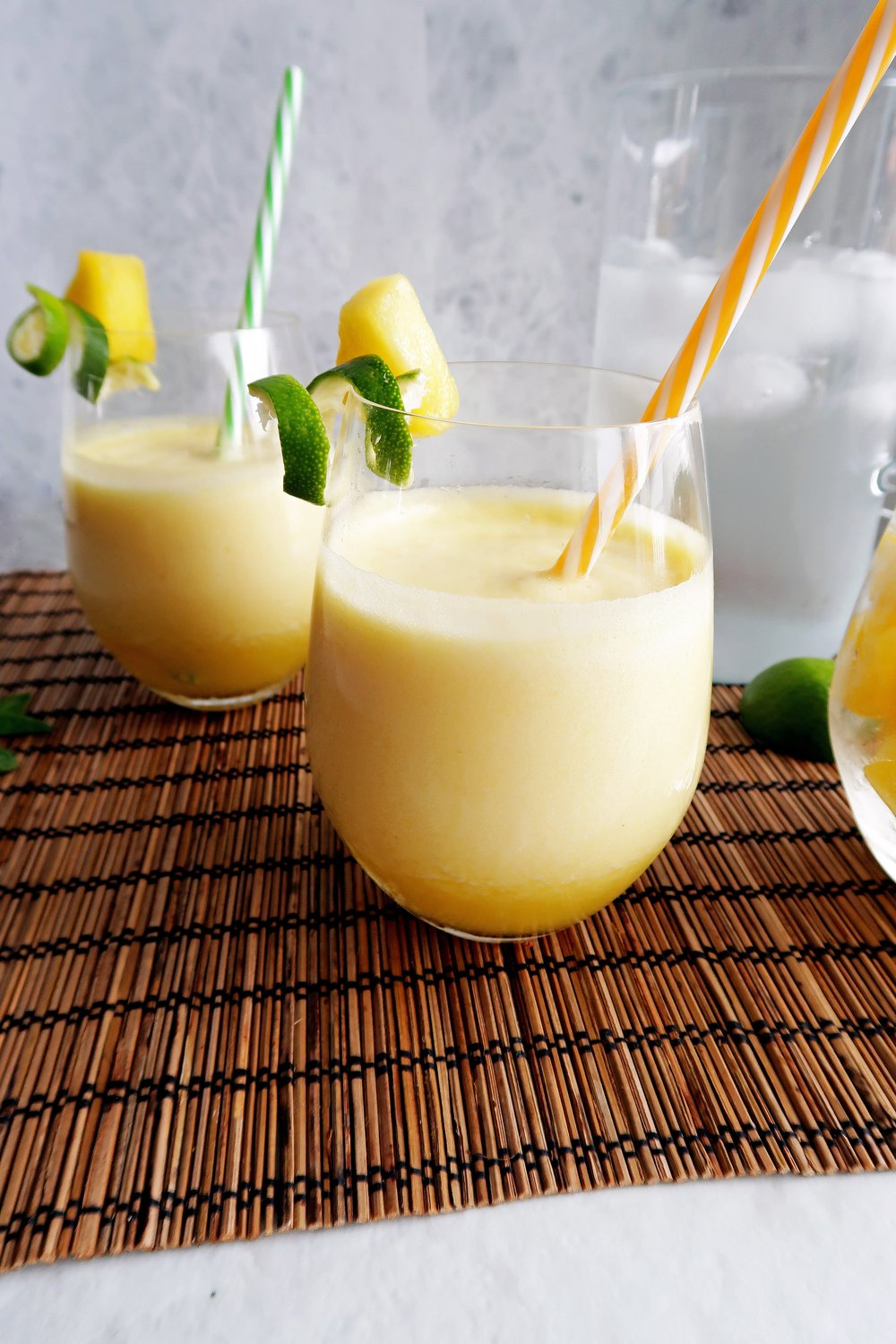 3-Ingredient Pineapple Coconut Water Slushies in two glasses with a yellow straw and pineapple and lime rind garnish.