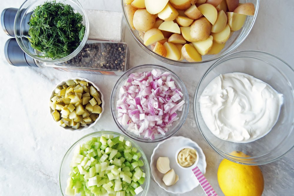 Separate bowls of potatoes, dill, onions,celery, red onions, and Greek yogurt ready to be combined into a potato salad.