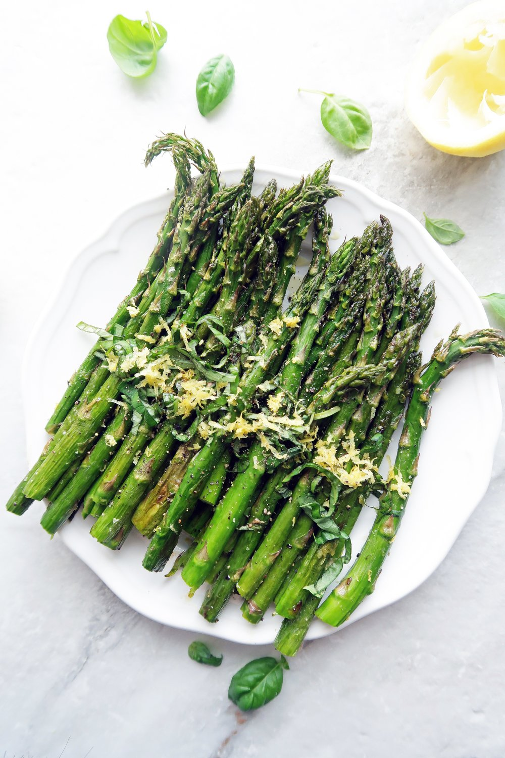Vegan and gluten-free quick roasted asparagus with lemon zest and sliced basil on a white plate.