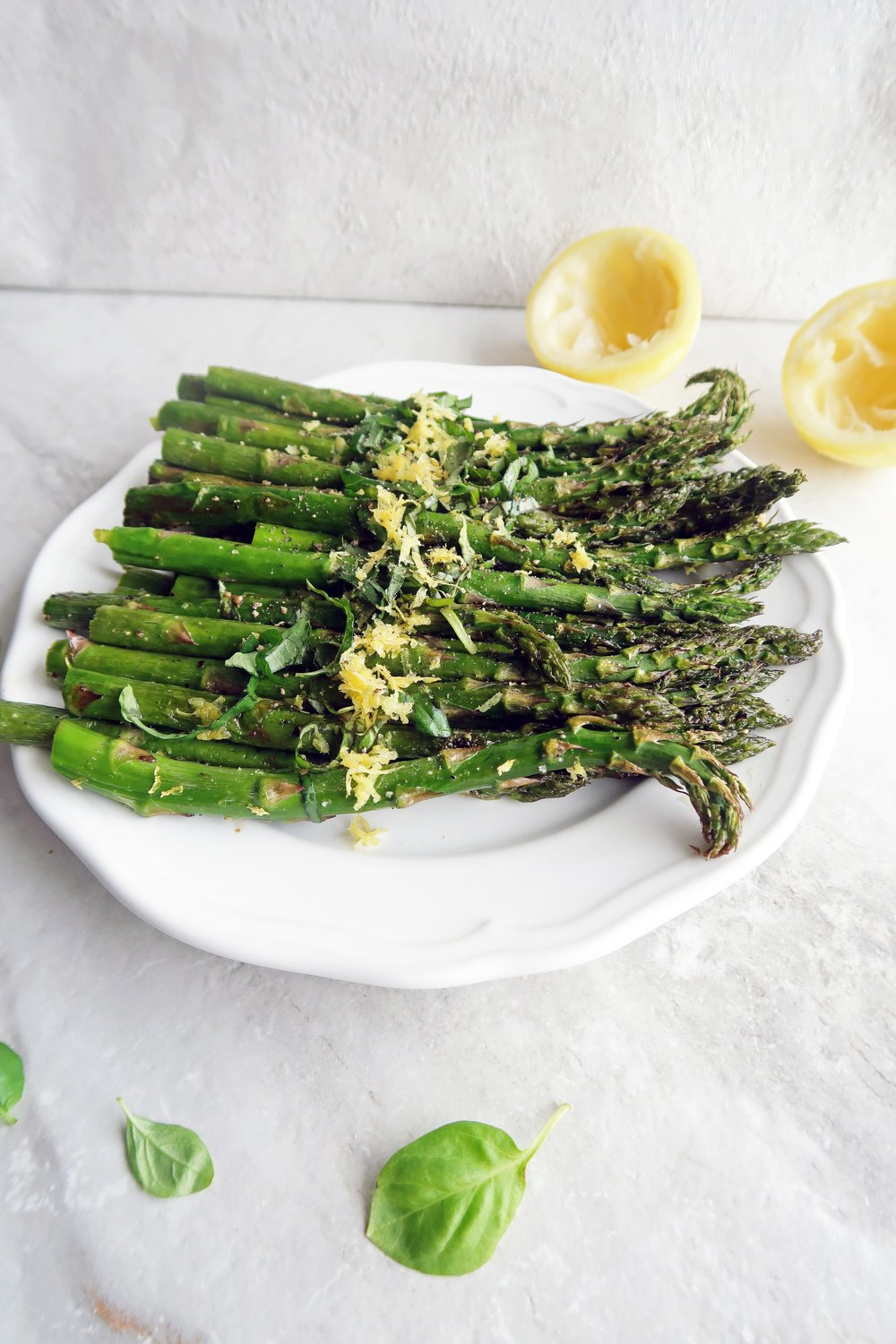 Vegan and gluten-free roasted asparagus with lemon and fresh basil on a white plate.