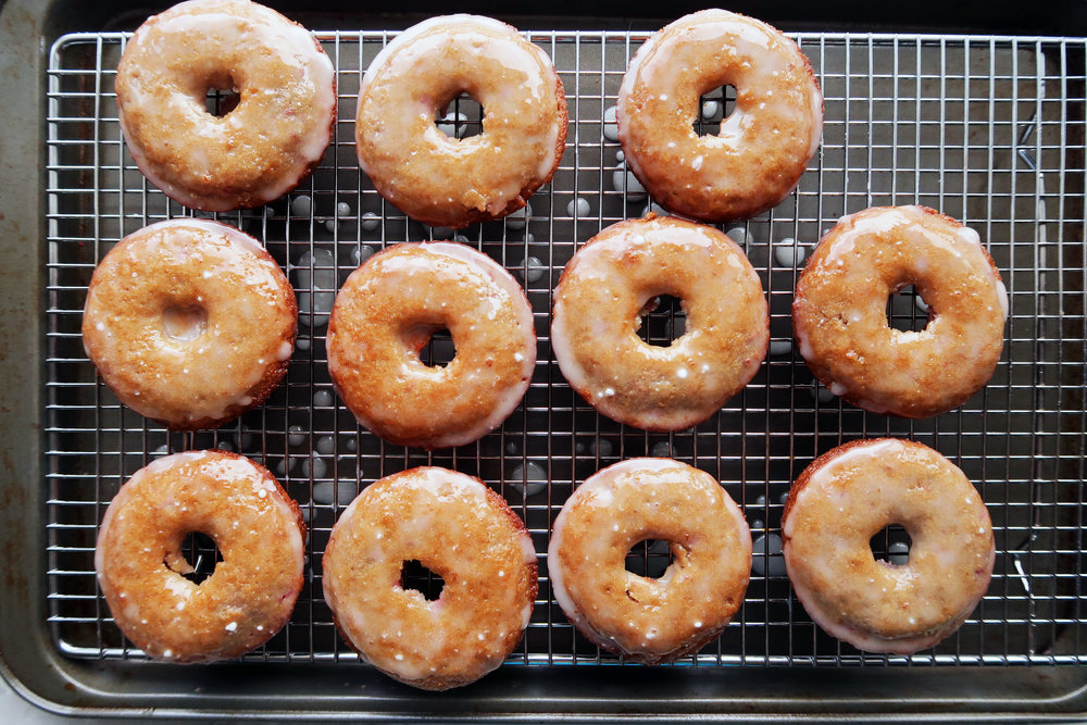 Ten Baked Raspberry Lemon Donuts that are freshly glazed on a cooling rack.