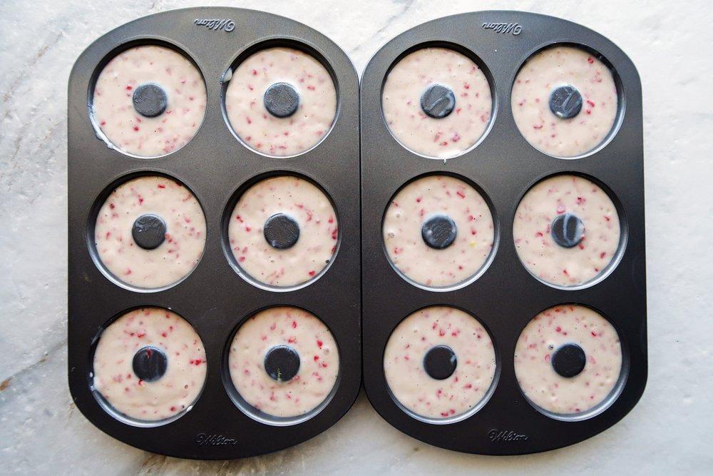 Donut pans filled with raspberry lemon batter.