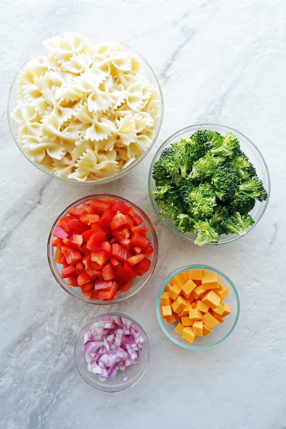 Bowls of bowtie pasta, broccoli, red bell peppers, cheddar cheese, and red onions.