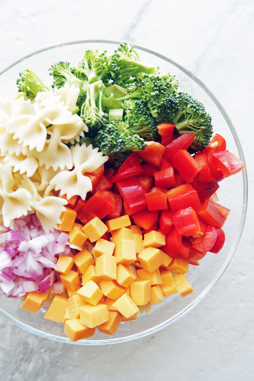 A big bowl of bowtie pasta, broccoli, red bell peppers, cheddar cheese, and red onions.