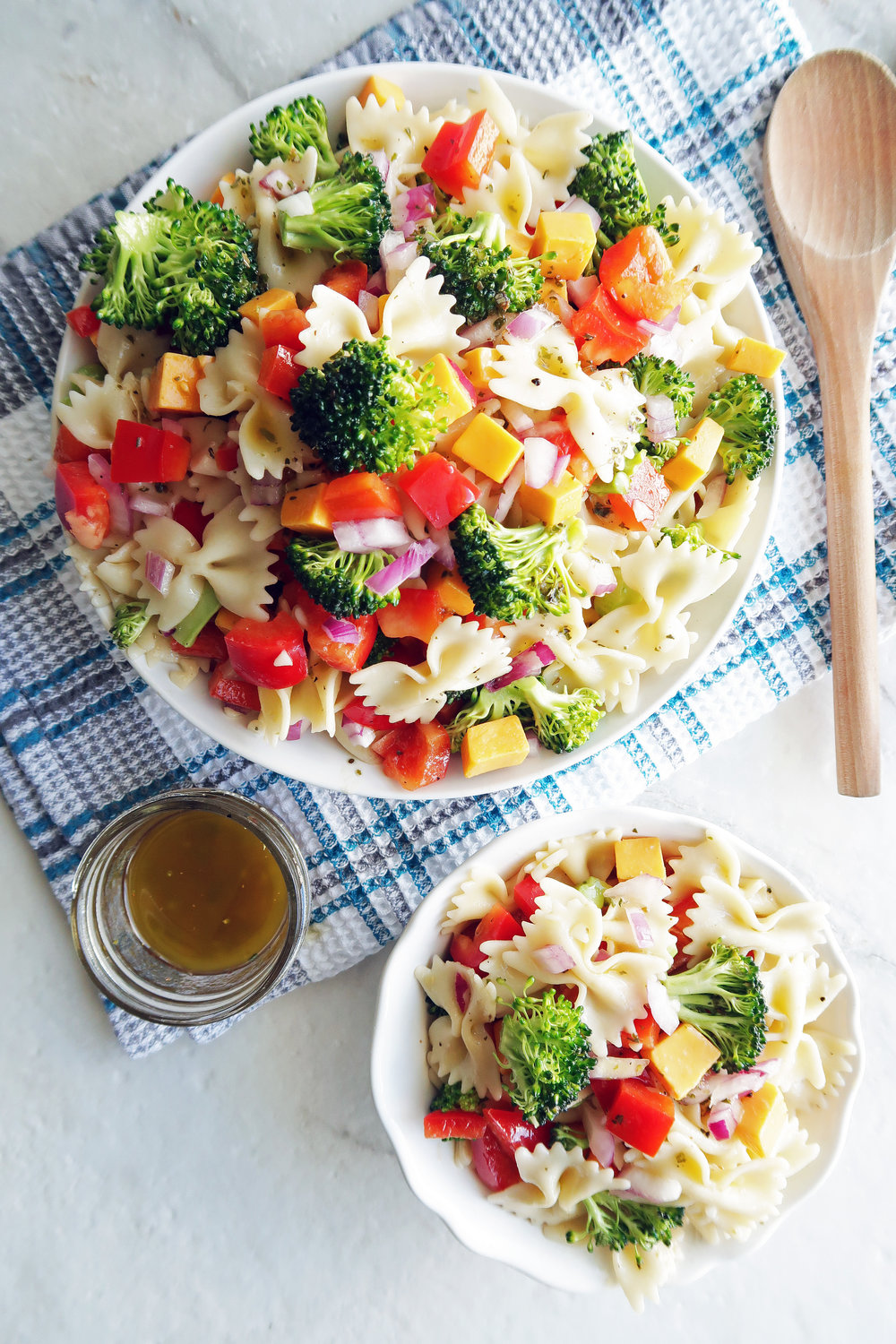 Broccoli Cheddar Pasta Salad with Tangy Italian Vinaigrette in a large pasta bowl, a small bowl of pasta salad, dressing in a small jar, and wooden spoon to the side.
