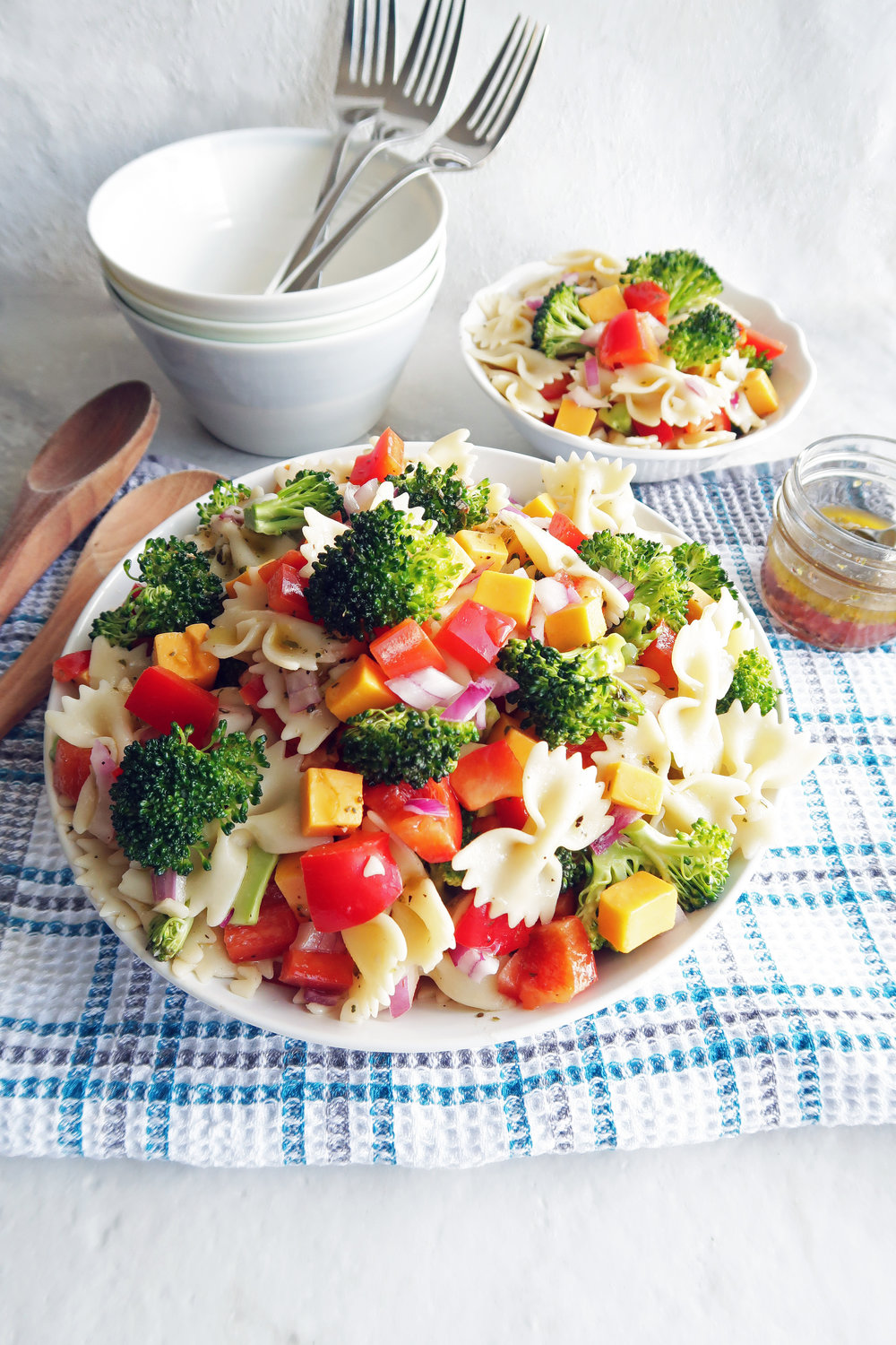 Broccoli Cheddar Pasta Salad with Tangy Italian Vinaigrette in a large pasta bowl, a small bowl of pasta salad, dressing in a small jar, and bowls and forks in the background.