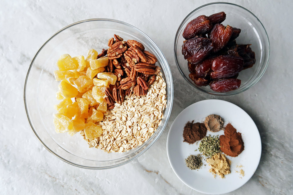 Bowls filled with dried dates, rolled oats, dried peaches, pecans, and chai spices.